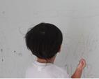 Menino feliz escrevendo na parede