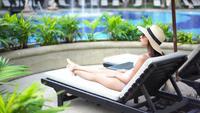 Mujer relajante junto a la piscina