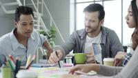 Grupo de empresarios casualmente vestidos discutiendo ideas en la oficina.