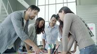 Groep terloops geklede bedrijfsmensen die ideeën in het bureau bespreken.