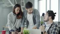 Groep terloops geklede bedrijfsmensen die ideeën in slimme vrijetijdskleding bespreken die aan laptop werken.