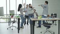 Homens e mulheres de negócios criativos asiáticos desfrutar e se divertir dançando enquanto trabalhava em seu escritório.