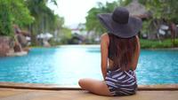 Vista posterior de la mujer sentada junto a la piscina