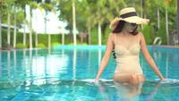 Mujer sentada junto a la piscina
