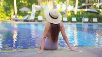 Vista posterior de la mujer junto a la piscina