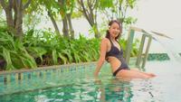 Mujer sentada junto a la piscina con plantas