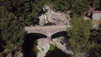 Drone volando de regreso revelando cascada y puente