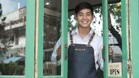 Young entrepreneur opens the door of his coffee shop