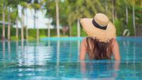 Hintere Ansicht des tragenden sunhat der Frau im Pool