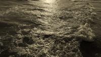 Vagues sur le sable pendant le lever du soleil