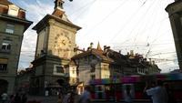 Gente en el callejón de compras con la torre del reloj de Berna en Suiza