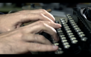 Writer Types On A Typewriter