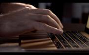 Um programador ou gravador digita em um teclado de laptop