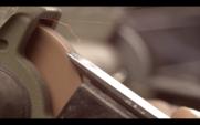 Um carpinteiro mói um cinzel em um moedor