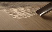 Entalhador esculpe um entalhe de cinzel no quadro