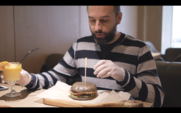 A Bearded Man Eating A Burger