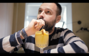 Un homme barbu buvant un cocktail