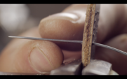 the master of working with leather flashes the strap with black thread. macro 4k