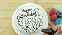 Woman is drawing chocolate on top of birthday butter cake decoration