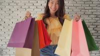 Mujer asiática joven que sostiene el bolso de compras