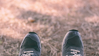 view of feet wearing sneakers waving side to side with grass background