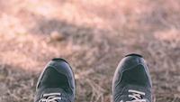 utsikt över fötter som bär sneakers som vinkar sida vid sida med gräsbakgrund