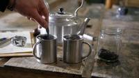 Close-up mãos derramando e misturando açúcar em xícaras de chá de Metal