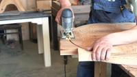 Een houtbewerker zaagt een rond tafelblad met een decoupeerzaag
