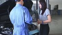 Asian Woman Listening to Auto Mechanic at  Garage Service Center
