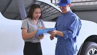 Auto Mechanic Giving Papers to Asian Woman to Sign