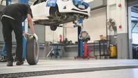 Mecánico masculino Rolling Tire en el garaje de servicio. Camara lenta