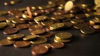 Um monte de moedas caindo sobre uma mesa de madeira