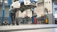 Hombre mecánico rodando un neumático para mantenimiento de automóviles