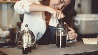Barista feminino asiático, fazendo café com uma imprensa francesa
