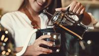 Barista feminino profissional asiática, servindo uma xícara de café