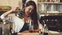 Barista feminino profissional asiático fazendo café na loja