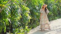 Joven mujer asiática camina en el jardín