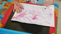 Niña dibuja con marcador sobre papel