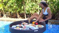 Junge asiatische Frau mit schwimmendem Frühstück am Pool