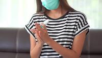 Een vrouw die een masker draagt en haar handen reinigt