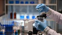 As mãos de um cientista misturando produtos químicos em um laboratório