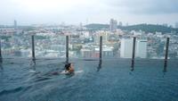 Asiatisk kvinna som simmar i en pool