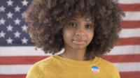 Ung svart kvinna som röstar med amerikanska flaggan på bakgrund