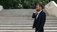 Empresário caminha no parque e fala ao telefone