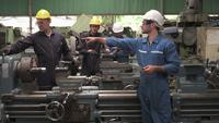 Arbeiter in Uniform inspizieren den Produktionslinienbereich.