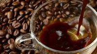 Gießen schwarzen Kaffee in eine Tasse