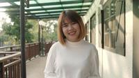 Aziatische vrouw die bij de camera glimlacht