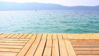 Grüner hölzerner Pier und ruhiges türkisfarbenes Meer