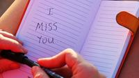 A woman Writes I Miss You In The Notebook