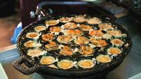 Fried egg with mussels cooking in iron pan